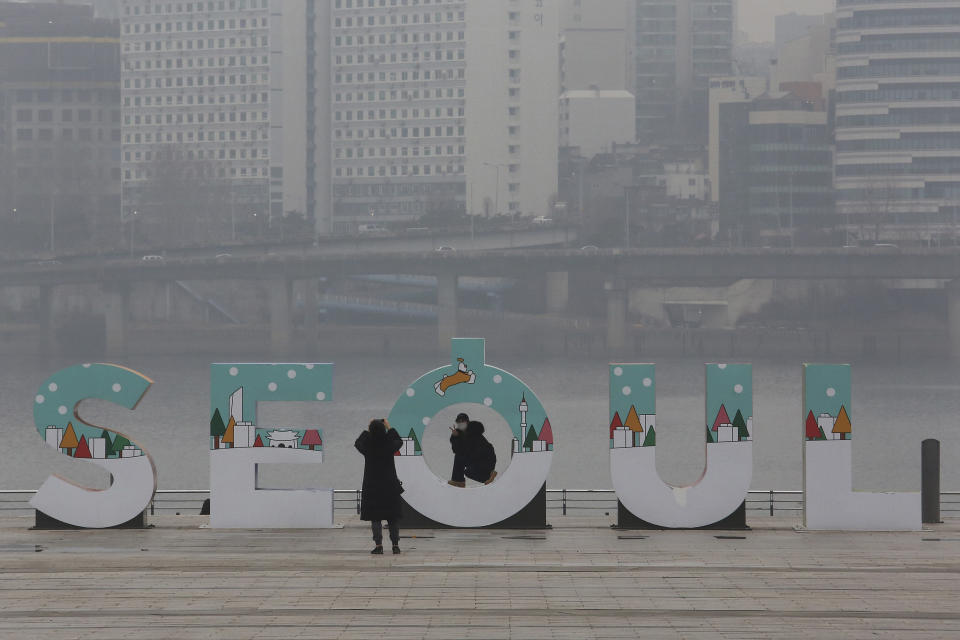 A woman wearing a face mask to help protect against the spread of the coronavirus poses for pictures at a park in Seoul, South Korea, Tuesday, Jan. 26, 2021. (AP Photo/Ahn Young-joon)