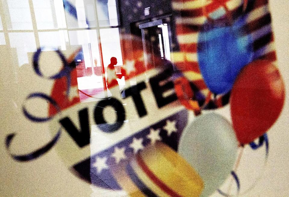 In this Nov. 1, 2016, photo, a voter is reflected in the glass frame of a poster while leaving a polling site in Atlanta, during early voting ahead of the Nov. 8 election day. Credit: AP Photo/David Goldman