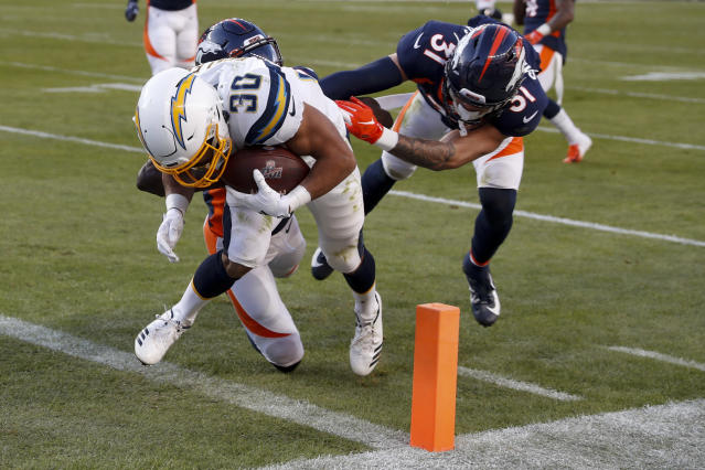 Los Angeles Chargers running back Austin Ekeler scores ahead of Denver Broncos cornerback Isaac Yiadom and free safety Justin Simmons, right, during the first half of an NFL football game Sunday, Dec. 1, 2019, in Denver. (AP Photo/David Zalubowski)