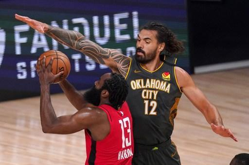 Houston Rockets' James Harden (13) goes up for a shot as Oklahoma City Thunder's Steven Adams (12) defends during the second half of an NBA first-round playoff basketball game, Monday, Aug. 31, 2020, in Lake Buena Vista, Fla. (AP Photo/Mark J. Terrill)