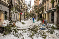 People walk along a street with snow and fallen tree branches during after a heavy snowfall in downtown Madrid, Spain, Sunday, Jan. 10, 2021. A large part of central Spain including the capital of Madrid are slowly clearing snow after the country's worst snowstorm in recent memory. (AP Photo/Manu Fernandez)