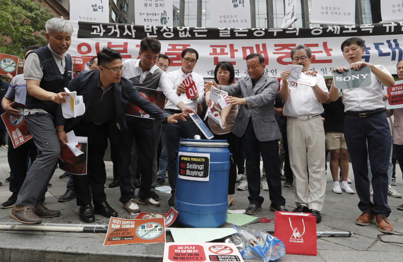 """South Korean small and medium-sized business owners throw papers showing logos of major Japanese brands into a trash can during a rally calling for a boycott of Japanese products in front of the Japanese embassy in Seoul, South Korea, Monday, July 15, 2019. South Korea and Japan last Friday, July 12, failed to immediately resolve their dispute over Japanese export restrictions that could hurt South Korean technology companies, as Seoul called for an investigation by the United Nations or another international body. The signs read: """"Our supermarket does not sell Japanese products."""" (AP Photo/Ahn Young-joon)"""