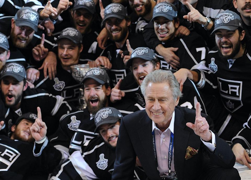 Los Angeles Kings owner Philip Anschutz, right, with his team pose for a group picture after beating the New Jersey Devils 6-1 in game 6 to win the Stanley Cup , Monday, June 11, 2012, in Los Angeles.