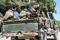 Fighters in a military force supporting Somali opposition leaders patrol a street in Mogadishu