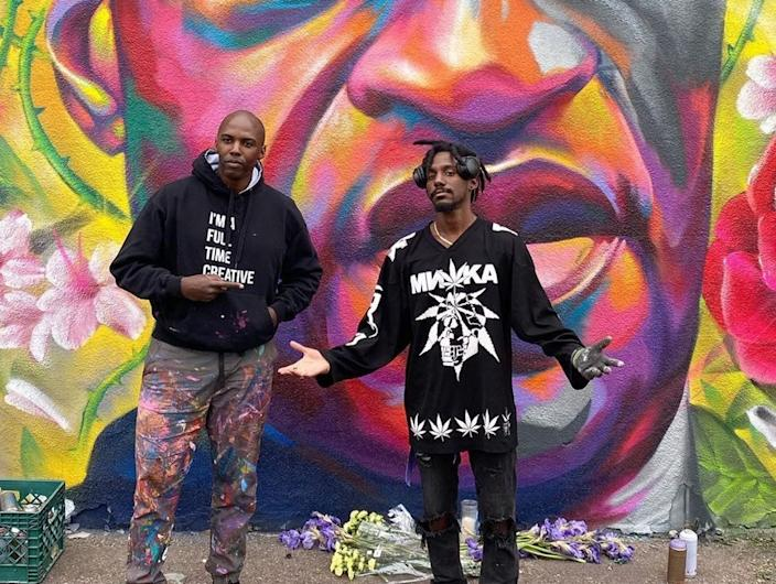 "Thomas ""Detour"" Evans and Hiero Veiga pose in front of their artwork."