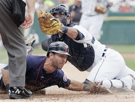 Detroit Tigers catcher Gerald Laird shows the ball to the umpire after tagging out Minnesota Twins' Darin Mastroianni, bottom, in the second inning of a baseball game Thursday, July 5, 2012, in Detroit. Mastroianni tried to score from third base on a hit by Jamey Carroll. (AP Photo/Duane Burleson)