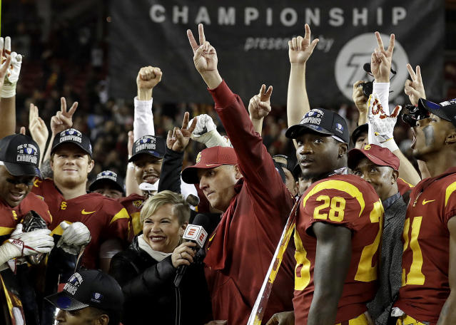 Southern California coach Clay Helton, center, gestures while being interviewed after his team defeated Stanford 31-28 in the Pac-12 Conference championship in Friday. (AP Photo/Marcio Jose Sanchez)