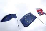 A Union Jack flag flutters next to EU flags outside the Houses of Parliament in London