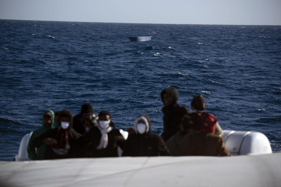 Migrants, most of them from Eritrea, are assisted by aid workers of the Spanish NGO Open Arms, after fleeing Libya on board a precarious wooden boat in the Mediterranean sea, about 110 miles north of Libya, on Saturday, Jan. 2, 2021. (AP Photo/Joan Mateu)