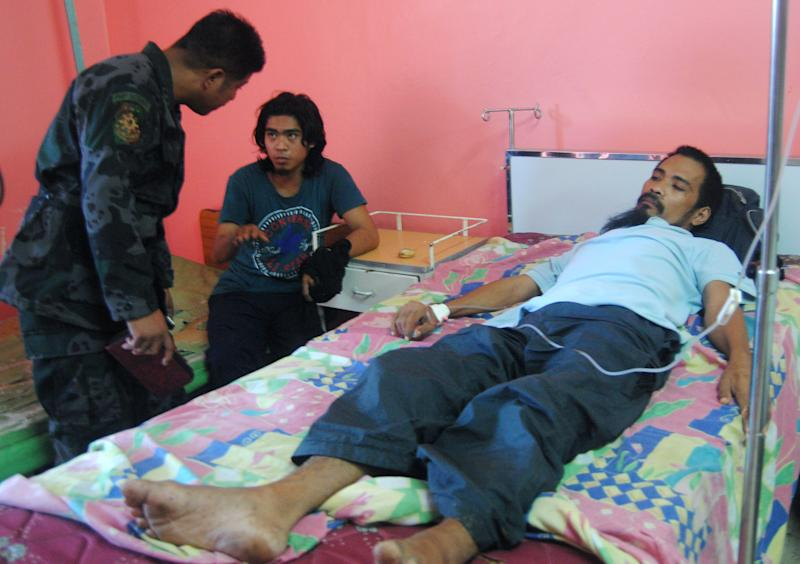 Roland Letriro, center, and Ramel Vela, Filipino members of a Jordanian TV journalist's crew believed to have been kidnapped by the al-Qaida-linked militants in June, talk to a police officer in their hospital room Sunday, Feb. 3, 2013, after being freed the night before on the volatile island of Jolo, Sulu province in southern Philippines. Policemen found frail-looking cameraman Vela and audio technician Letriro late Saturday and brought them to a hospital in southern Sulu province, where they were kidnapped in June along with Jordanian Baker Abdulla Atyani, provincial police chief Senior Superintendent Antonio Freyra said. Atyani is believed to still be held by the gunmen.(AP Photo/Nickee Butlangan)