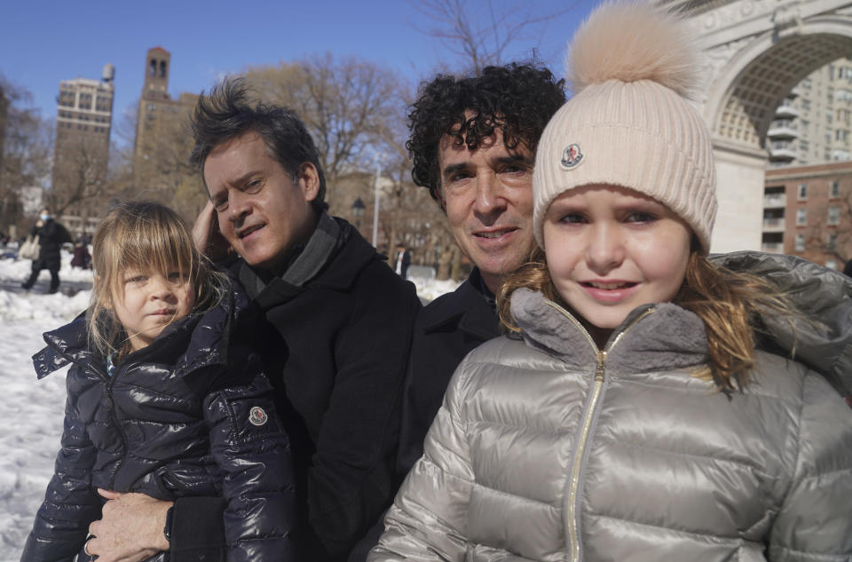 New York State Senator Brad Hoylman, left, with his husband David Sigal, right, pose with their daughters Lucy Hoylman-Sigal, 3, left, and Silvia Hoylman-Sigal, 10, both born through surrogacy, Saturday Feb. 6, 2021, in New York. Sen. Hoylman is the lead sponsor of a New York State law taking effect on Feb. 15 that legalizes commercial surrogacy. (AP Photo/Bebeto Matthews)