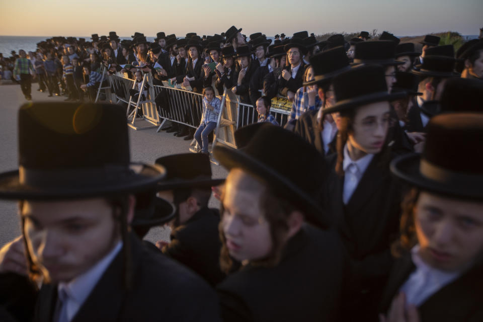 """Ultra-Orthodox Jews of the Kiryat Sanz Hassidic sect listen to their rabbi on a hill overlooking the Mediterranean Sea as they participate in a Tashlich ceremony, in Netanya, Israel, Tuesday, Sept. 14, 2021. Tashlich, which means """"to cast away"""" in Hebrew, is the practice in which Jews go to a large flowing body of water and symbolically """"throw away"""" their sins by throwing a piece of bread, or similar food, into the water before the Jewish holiday of Yom Kippur, which starts at sundown on Wednesday. (AP Photo/Ariel Schalit)"""