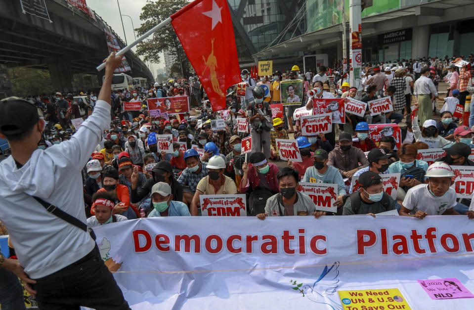 Demonstrators hold pictures of deposed Myanmar leader Aung San Suu Kyi and placards during a protest against the military coup in Yangon, Myanmar Thursday, Feb. 18, 2021. Demonstrators against Myanmar's military takeover returned to the streets Thursday after a night of armed intimidation by security forces in the country's second biggest city. (AP Photo)