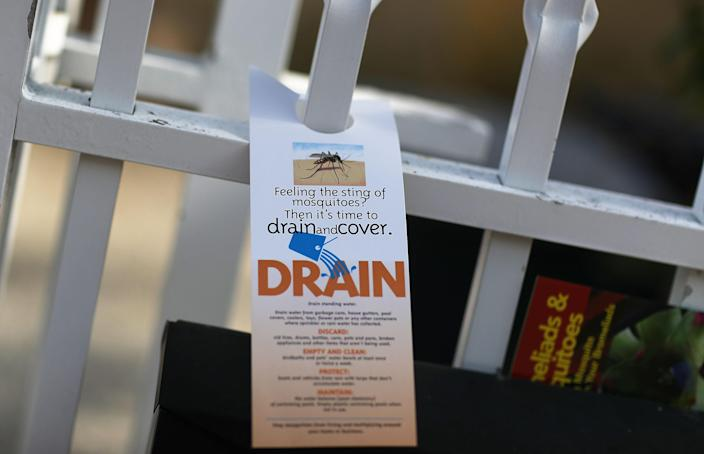 A pamphlet educating people about mosquitoes hangs on a fence in 2017 as workers with Miami-Dade County Mosquito Control inspect a neighborhood for mosquitoes or areas where they breed, as the county works to eradicate mosquitoes carrying the Zika virus. (Photo: Joe Raedle/Getty Images)