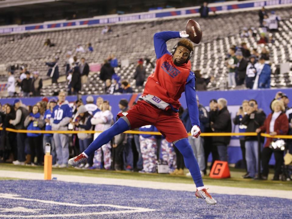 FILE - In this Nov. 23, 2014, file photo, New York Giants wide receiver Odell Beckham Jr. makes a one-handed catch while warming up to play against the Dallas Cowboys in an NFL football game in East Rutherford, N.J. The one-handed catch by Odell Beckham Jr. that became the most talked-about play from Sunday did more than just boost his standing with the New York Giants, it paid off a routine growing popular among many skill players of practicing the impractical, one-handed circus grab. (AP Photo/Kathy Willens, File)