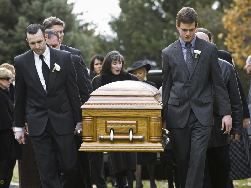 Mourners carrying a coffin at a funeral.