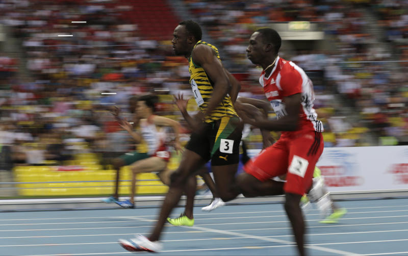 Jamaica's Usain Bolt, left, and Trinidad and Tobago's Rondel Sorrillo compete in a men's 100-meter heat at the World Athletics Championships in the Luzhniki stadium in Moscow, Russia, Saturday, Aug. 10, 2013. (AP Photo/David J. Phillip)