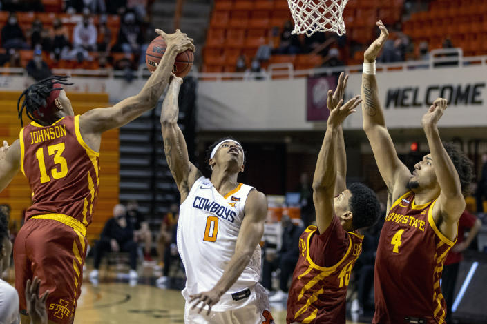 Iowa State forward Javan Johnson (13) blocks Oklahoma State guard Avery Anderson III (0) shot as Iowa State's Rasir Bolton and George Conditt IV guard the lane during the second half of the NCAA college basketball game in Stillwater, Okla., Tuesday, Feb. 16, 2021. (AP Photo/Mitch Alcala)