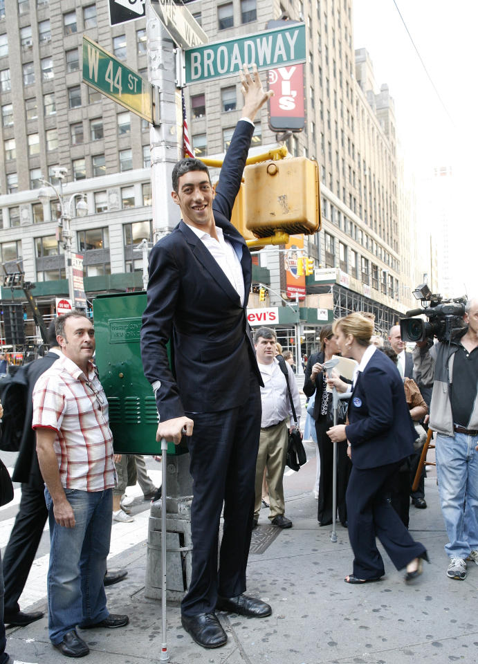 The world's tallest man, Sultan Kosen of Turkey, poses for photographers in New York's Times Square, September 21, 2009. The 26-year-old is 2 metres 46.5 cm (8 feet 1 inch) tall, also claiming the record for the largest hands and feet. Kosen is in New York to promote the Guinness book of World Records 2010. REUTERS/Brendan McDermid (UNITED STATES SOCIETY ENTERTAINMENT)