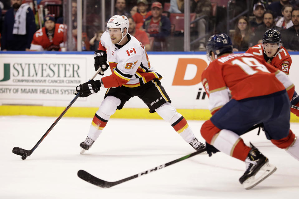 FILE - Calgary Flames center Sam Bennett (93) takes the puck down the ice against Florida Panthers defenseman Mike Matheson (19) and center Frank Vatrano (77) during the first period of an NHL hockey game in Sunrise, Fla., in this Sunday, March 1, 2020, file photo. All divisional play during this shortened NHL season gives an added perk to most of the players traded at the deadline: They'll get to face different teams. After months of worrying only about the six other Canadian teams and not paying attention to the rest of the league, Sam Bennett will get to play against six Central Division opponents after a trade to the Panthers. (AP Photo/Wilfredo Lee, File)