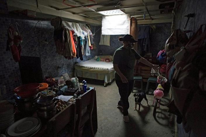 Carla is seen at the room where she lives with her daughters and her father, which used to be a bathroom, at a shelter located in the basement of the Sudameris public building in Caracas