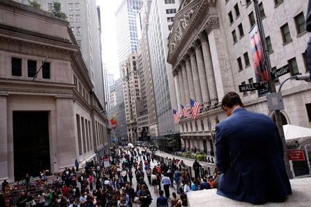A man sits on a marble wall as pedestrians walk on the streets in front of the New York Stock Exchange in New York