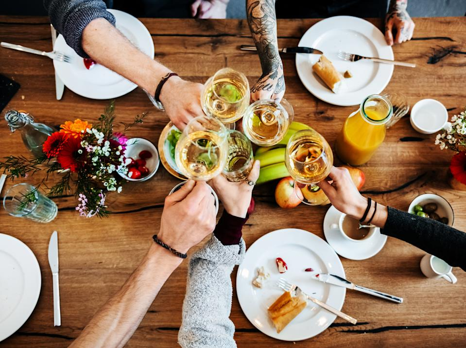 Young people sitting in a bright café are having a toast with glasses of white wine during dinner. The glasses are seen from bird's eye view while there is food and flowers on the table.