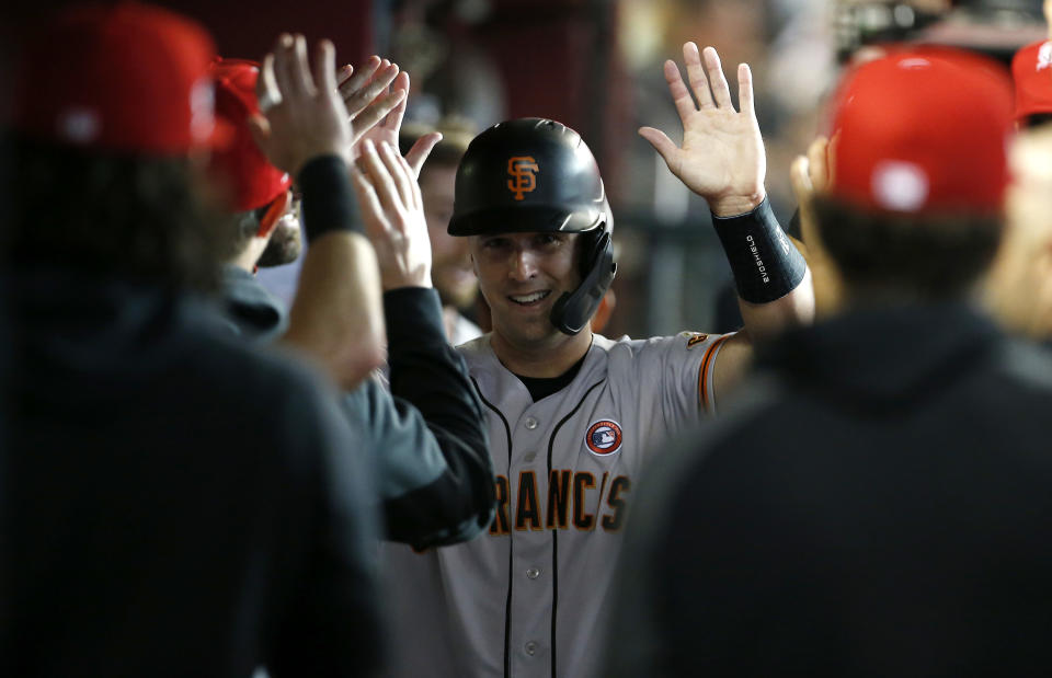 PHOENIX, ARIZONA - JULY 04: Buster Posey #28 of the San Francisco Giants is congratulated by teammates after scoring against the Arizona Diamondbacks on an RBI double by Darin Ruf #33 of the Giants during the first inning of the MLB game at Chase Field on July 04, 2021 in Phoenix, Arizona. (Photo by Ralph Freso/Getty Images)