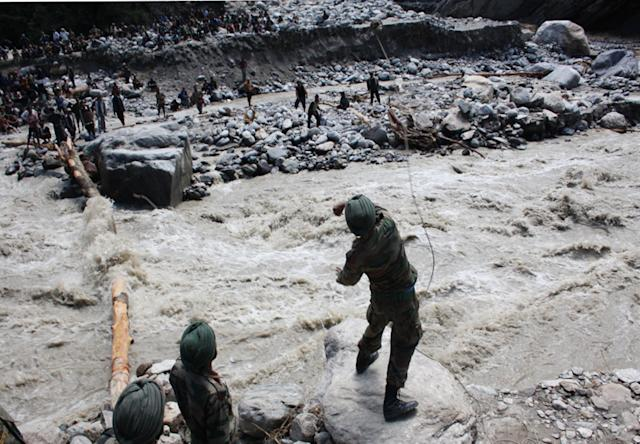 "In this handout photograph released by the Indian Ministry of Defence, Indian military personnel throw a rock with a rope attached across a river to help rescue pilgrims in Uttarakhand state, on June 22, 2013. Relief teams were racing against time June 22 to rescue tens of thousands of stranded people in rain-ravaged northern India as the death toll from flash floods and landslides neared 600. Floods and landslides from monsoon rains have also struck neighbouring Nepal, leaving at least 39 people dead, the Nepalese government said. AFP PHOTO/MINISTRY OF DEFENCE----EDITORS NOTE---- RESTRICTED TO EDITORIAL USE - MANDATORY CREDIT - ""AFP PHOTO/MINISTRY OF DEFENCE"" - NO MARKETING NO ADVERTISING CAMPAIGNS - DISTRIBUTED AS A SERVICE TO CLIENTS -----"