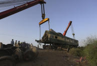 Railway workers use crane to remove wreckage to clear the track at the site of a train collision in the Ghotki district, southern Pakistan, Tuesday, June 8, 2021. The death toll from a deadly train accident in southern Pakistan jumped to dozens on Tuesday after rescuers pulled a dozen more bodies from crumpled cars of two trains that collided on a dilapidated railway track a day ago, an official said, as rescue work continued even 24 hours after the incident to find any survivors. (AP Photo/Fareed Khan)