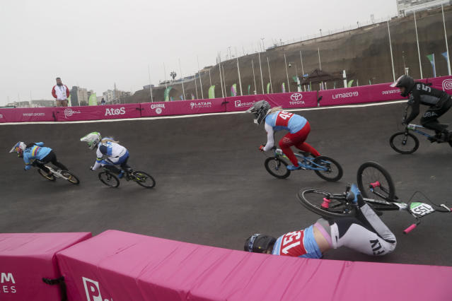 Mariana Pajon of Colombia leads as Drew Mechielsen of Canada falls in a women's cycling BMX heat at the Pan American Games in Lima, Peru, Friday, Aug. 9, 2019. (AP Photo/Fernando Llano)