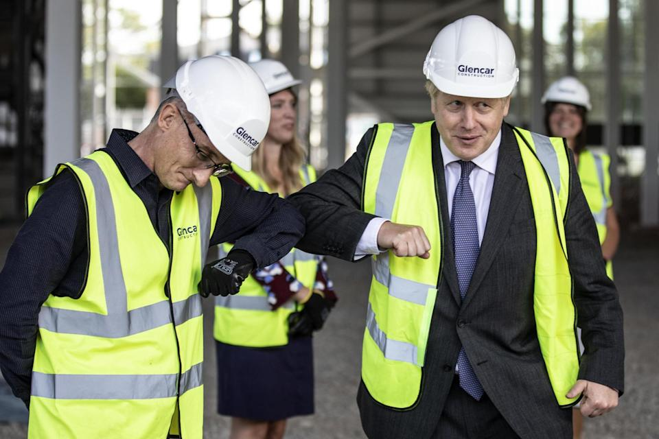 Boris Johnson bumps elbows with scientists as he visits the construction site of the new vaccines Manufacturing and Innovation Centre (PA)