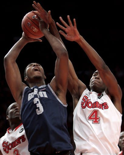 St. John's Moe Harkless, right, fouls Georgetown's Mikael Hopkins during the first half of an NCAA college basketball game in New York, Sunday, Jan. 15, 2012. (AP Photo/Seth Wenig)