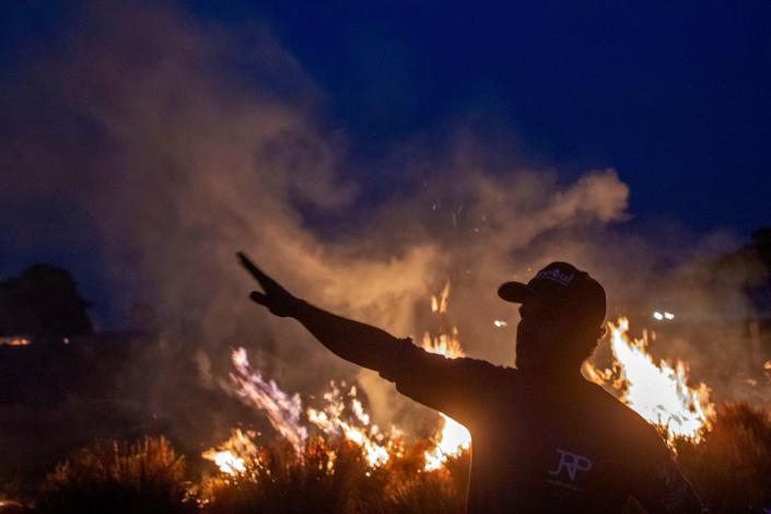 A laborer gestures as he looks at a fire that spread to the farm he works on next to a highway in Nova Santa Helena municipality in northern Mato Grosso State, south in the Amazon basin in Brazil, on Aug. 23, 2019. (Photo: Joao Laet/AFP/Getty Images)