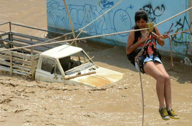 Residents of the Huachipa populous district, east of Lima, are helped on March 17, 2017, by police and firemen rescue teams to cross over flash floods hitting their neighbourhood and isolating its residents