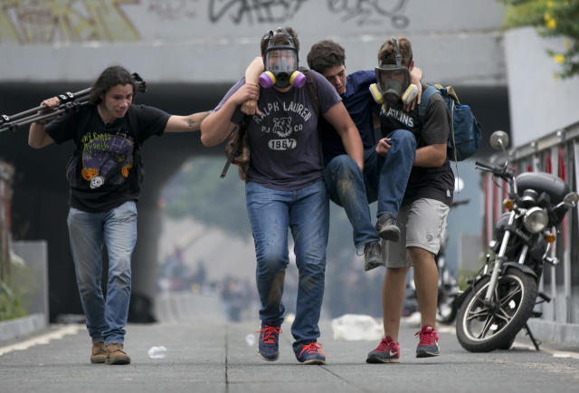 <p>Demonstrators carry a youth away from tear gas fired by police during an opposition demonstration in Caracas, June 7, 2016. Protesters attempted to march to demand that government pursue a recall referendum against President Nicolas Maduro. (AP/Ariana Cubillos) </p>