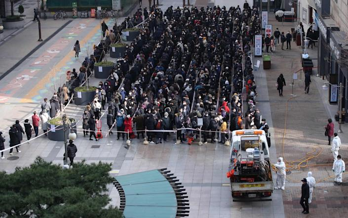 Residents in Daegu wait in line to buy face masks on Tuesday - YONHAP/AFP via Getty Images