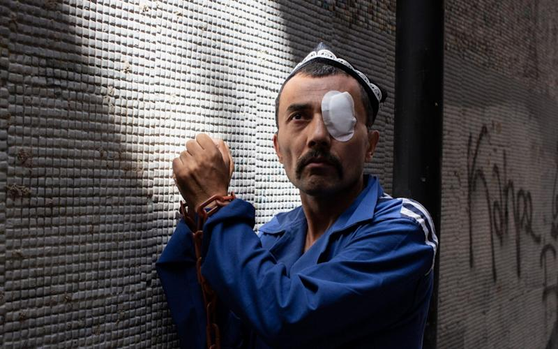 A Uighur activist wears plastic chains and an imitation prison uniform ahead of a demonstration outside the Chinese embassy in Istanbul - Sam Tarling for The Telegraph