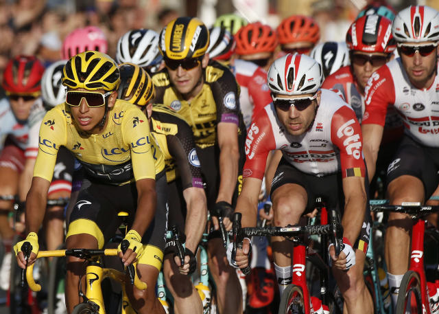 FILE - In this Sunday, July 28, 2019 file photo, Colombia's Egan Bernal, left, wearing the overall leader's yellow jersey, center, races on the Champs Elysees during the Tour de France cycling race in Paris. The team of reigning Tour de France champion Egan Bernal has withdrawn from all races over the next three weeks amid the spread of the new virus outbreak and following the death of one of its sports directors. (AP Photo/Michel Euler, File)