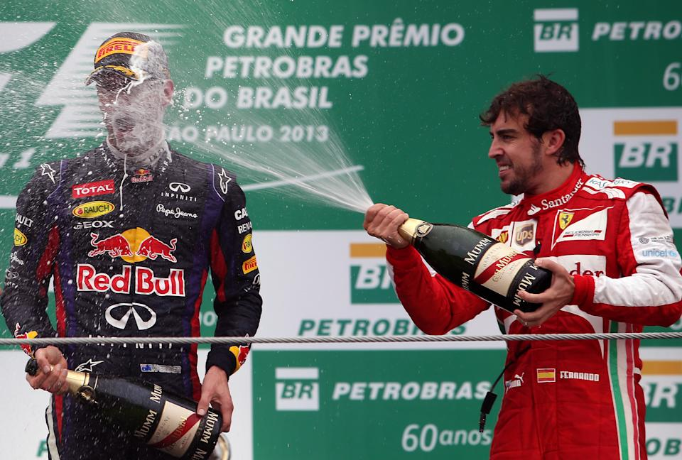 Australian Mark Webber (L) of Red Bull celebrates his second place with Spanish Fernando Alonso of Ferrari (R-third) in the podium of the Brazilian Formula one Grand Prix at the Interlagos racetrack in Sao Paulo, Brazil, on November 24, 2013.                    AFP PHOTO/MIGUEL SCHINCARIOL        (Photo credit should read Miguel Schincariol/AFP via Getty Images)