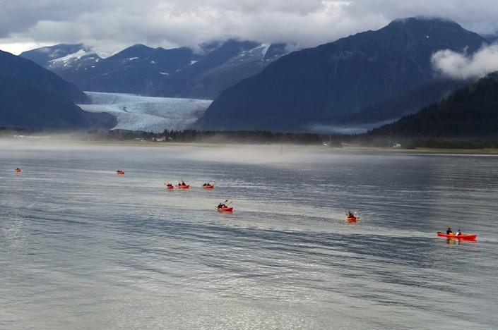 Kayakers are nearing shore on Douglas Island, with Mendenhall Glacier seen in the background in 2016, in Juneau, Alaska. (Becky Bohrer/AP)
