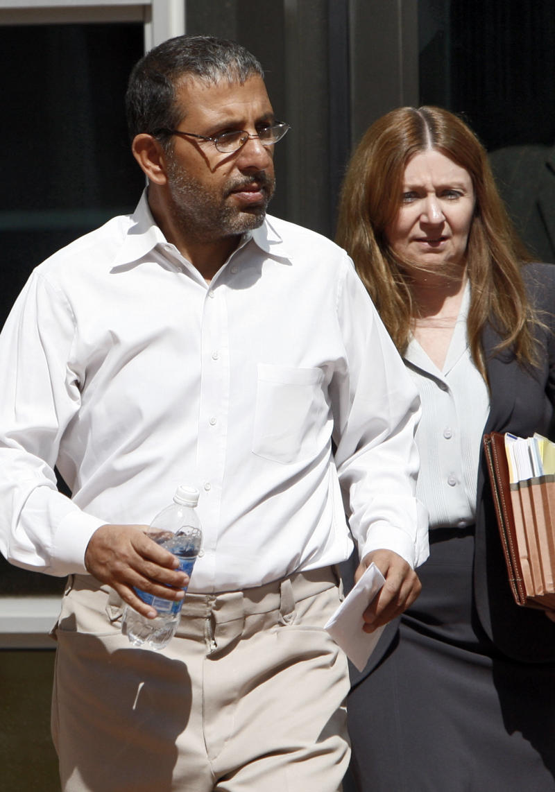 FILE - In this Sept. 24, 2009 file photo, Mohammed Wali Zazi, left, leaves the federal courthouse in Denver with U.S. Marshals. Zazi, who previously pleaded not guilty to conspiracy in the terror case against his son, Najibullah Zazi, was charged by federal prosecutors in New York with obstruction of justice and other counts on Tuesday, Nov. 30, 2010. Najibullah Zazi pleaded guilty to terrorism charges in February 2010, of plotting to bomb New York City subways in 2009. (AP Photo/Ed Andrieski, File)
