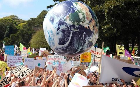 Protesters push an inflatable globe into the air while holding placards and banners during the Global Climate Strike demonstration at the Domain in Sydney - Credit: David Gray/Bloomberg