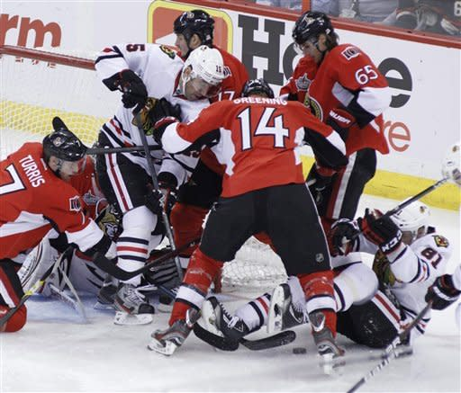Chicago Blackhawks' Andrew Brunnette (15) and teammate Mirian Hossa (81) battle for the puck with Ottawa Senators' Kyle Turris (7) Colin Greening (14) and Erik Karlsson (65) in front of the Senators' net along during first-period NHL hockey game action in Ottawa, Ontario, Friday, March 2, 2012. (AP Photo/The Canadian Press, Fred Chartrand)