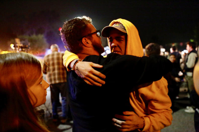 "Holden Harrah, 21, (right), who witnessed the shooting at Borderline Bar & Grill late Wednesday, hugs family and friends.<a href=""https://www.huffingtonpost.com/entry/photos-show-scene-outside-thousand-oaks-bar-after-mass-shooting-leaves-12-dead_us_5be44733e4b0e8438894d380#5be44559e4b0e8438894ca2a""></a> (Al Seib via Getty Images) (Al Seib via Getty Images)"