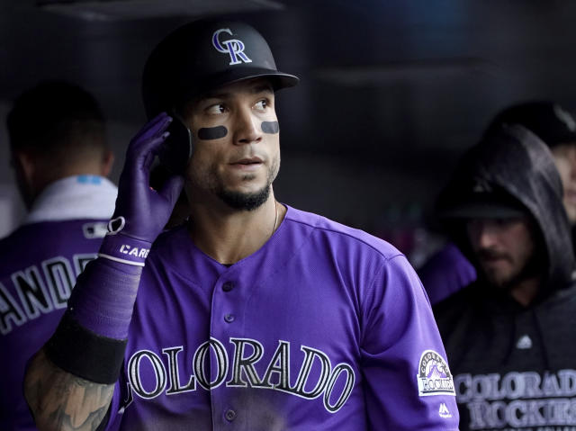 FILE - In this June 18, 2018, file photoColorado Rockies' Carlos Gonzalez walks in the dugout after scoring against the New York Mets during the second inning of a baseball game in Denver. A person familiar with the agreement says Gonzalez intends to sign a minor league contract with the Cleveland Indians. Gonzalez, who played the past 10 seasons with Colorado, will sign once he completes a physical and join the Indians at spring training, said the person who spoke Saturday, March 16, to The Associated Press on condition of anonymity because the deal has not been finalized. (AP Photo/Jack Dempsey, File)