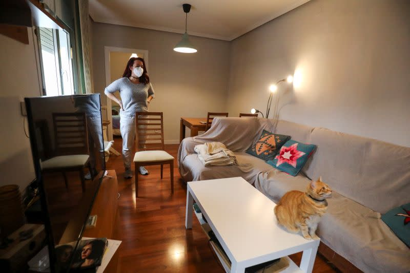 Ines Alcolea stands in the dining room before leaving her rented apartment in Madrid