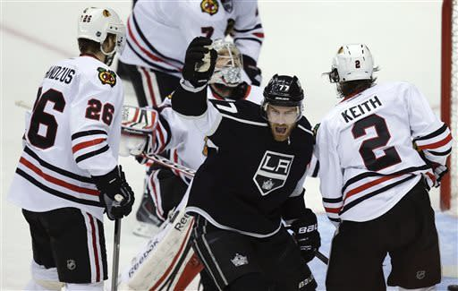 Los Angeles Kings center Jeff Carter (77) reacts after a goal by defenseman Slava Voynov against Chicago Blackhawks goalie Corey Crawford, behind Carter, during the second period of Game 3 of the NHL hockey Stanley Cup playoffs Western Conference finals, Tuesday, June 4, 2013, in Los Angeles. (AP Photo/Jae C. Hong)