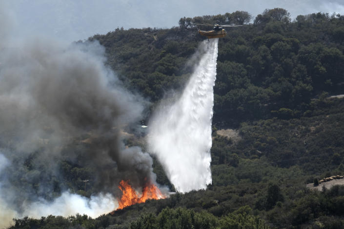 A helicopter drops water on a wildfire Wednesday, Oct. 13, 2021, in Goleta, Calif. A wildfire raging through Southern California coastal mountains threatened ranches and rural homes and kept a major highway shut down Wednesday as the fire-scarred state faced a new round of dry winds that raise risk of infernos. (AP Photo/Ringo H.W. Chiu)