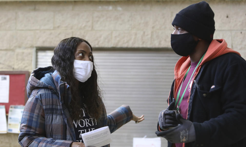 Community outreach worker Donyell Wynn, left, talks with Will Jones in Chicago on Tuesday, Feb. 23, 2021. Jones said he was interested in being vaccinated against COVID-19, but wanted more information first. Wynn was enlisted by Saint Anthony Hospital to promote vaccination in hard hit Black and brown neighborhoods. (AP Photo/Teresa Crawford)